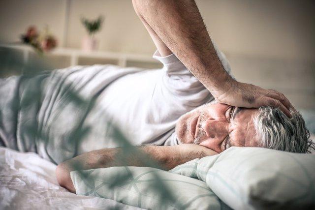 Dormir mal, dolor de cabeza, hombre en la cama