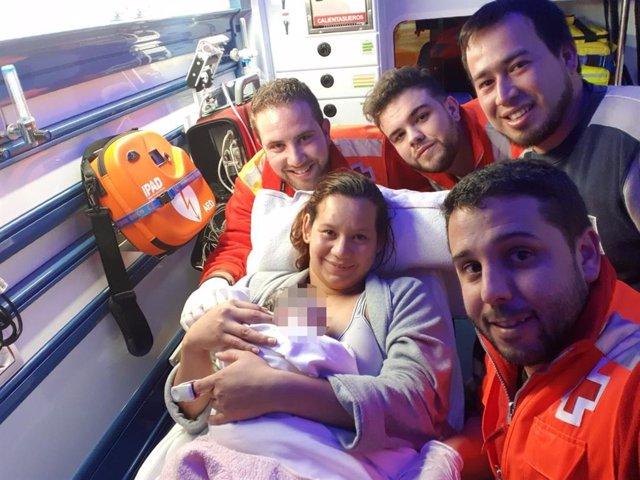 La dotación de Cruz Roja posa con la parturienta en el interior de la ambulancia