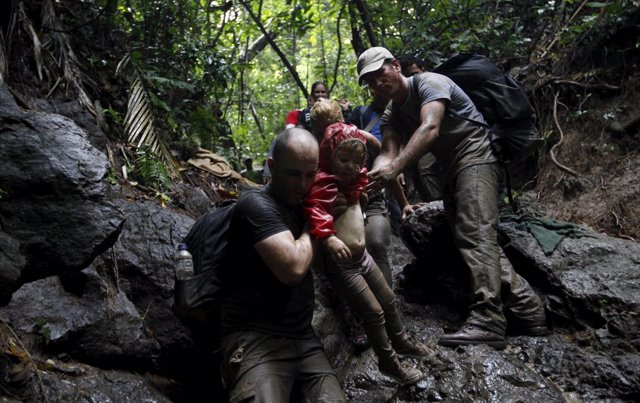 Cuban migrants help to carry a child as they climb down a slope crossing the bor