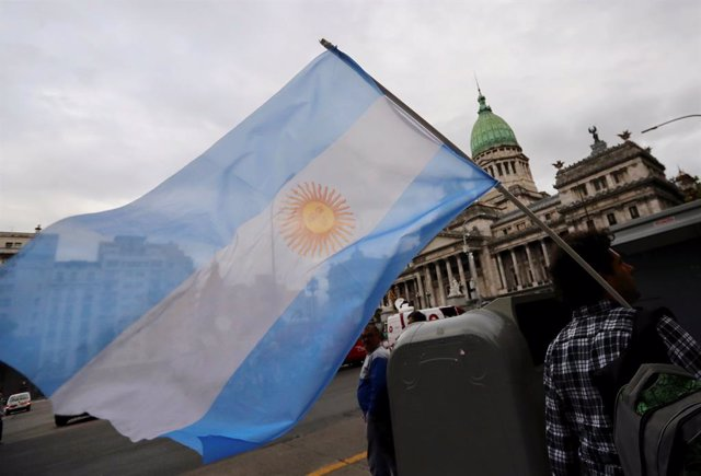 A man waves an Argentine national flag during a protest against a cost increase