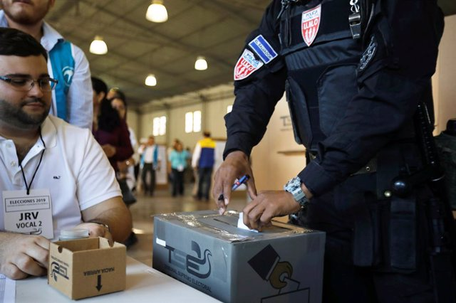 A police officer casts his vote during the presidential election in San Salvador