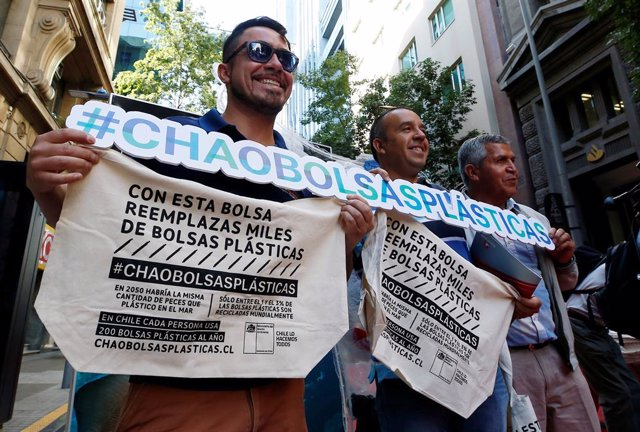 """People pose for the media with a placard that reads: """"Goodbye Plastic Bags"""", aft"""