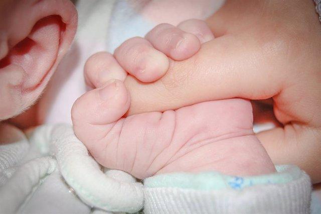 Un bebè agafa un dit d'una mà