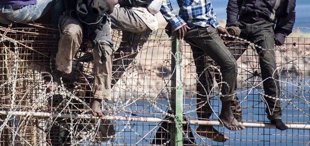 Inmigrantes africanos encaramados a la valla de Melilla con concertinas