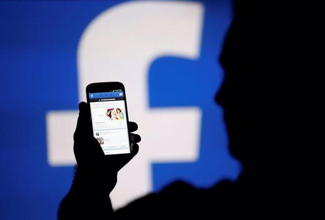 Pantalla de móvil frente al logotipo de Facebook