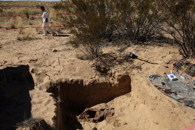A forensic technician walks by a clandestine grave with skeleton remains at an a