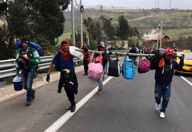 Migrantes venezolanos caminan por una carretera de Ecuador hacia Perú