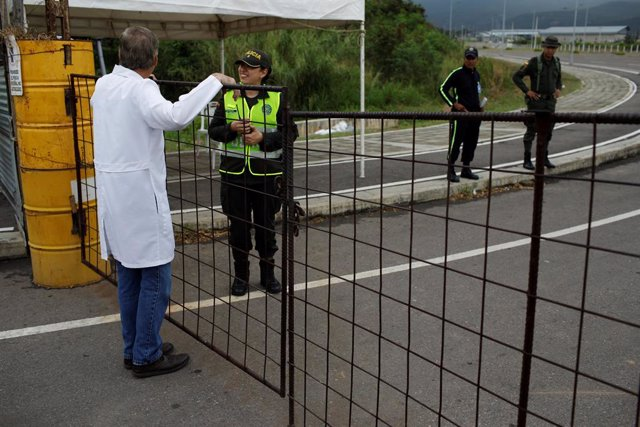 A Venezuelan doctor speaks with a Colombian police officer during a gathering at
