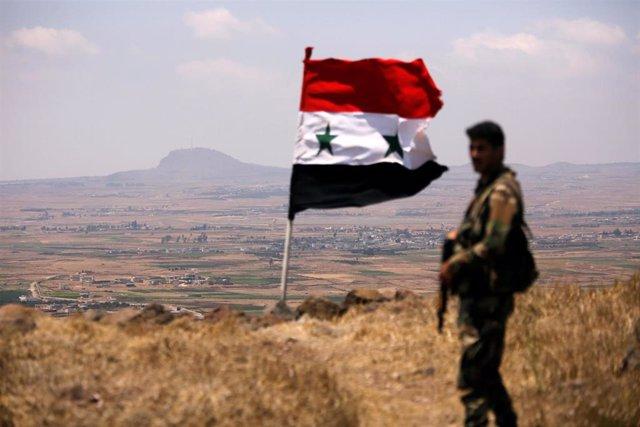 Un soldado sirio junto a la bandera nacional en Quneitra