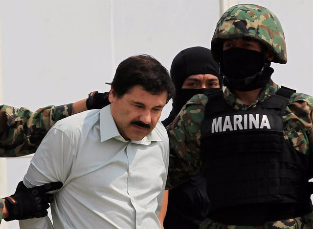 "Joaquin ""El Chapo"" Guzman (L) is escorted by soldiers during a presentation at t"