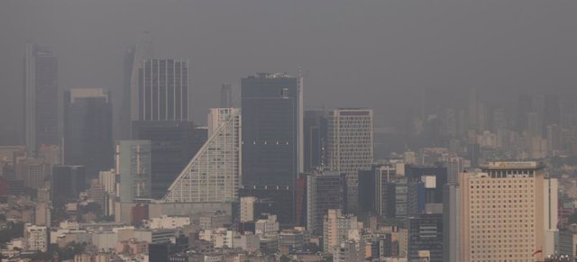 Buildings stand shrouded in smog during an environmental contingency day in Mexi