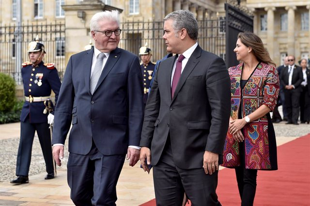 German President Frank-Walter Steinmeier walks alongside Colombian President Iva