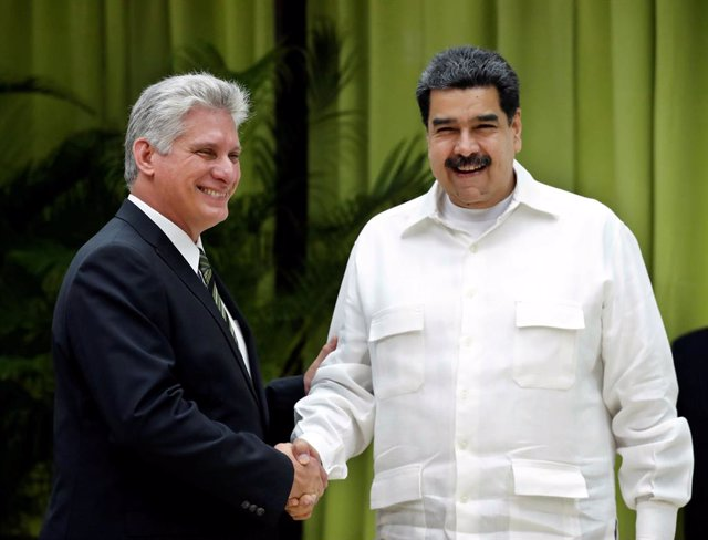 Cuba's President Miguel Diaz-Canel (L) shakes hands with Venezuela's President N
