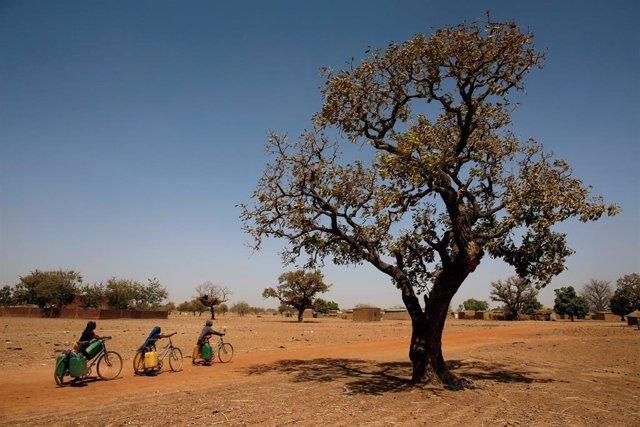 Niñas transportando agua en bicicletas cerca de Uagadugú