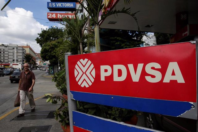 A man walks past the corporate logo of the state oil company PDVSA at a gas stat