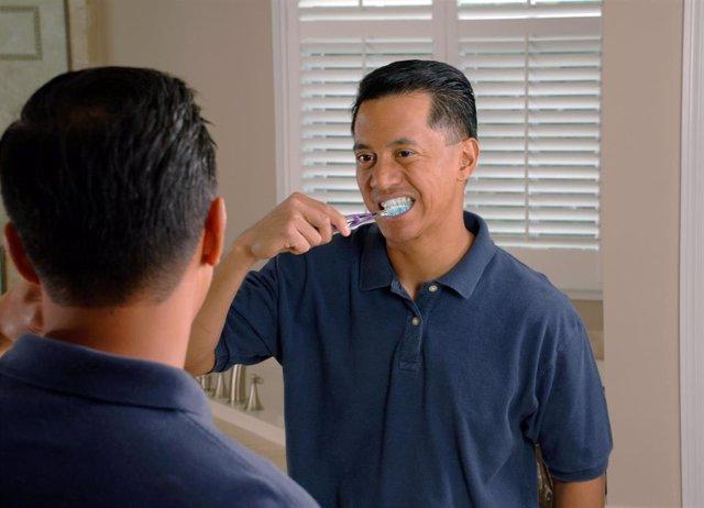 Un hombre se cepilla los dientes