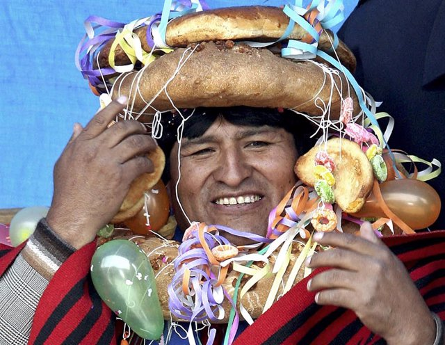 Bolivia's President Evo Morales wears a traditional headdress and wreath made of
