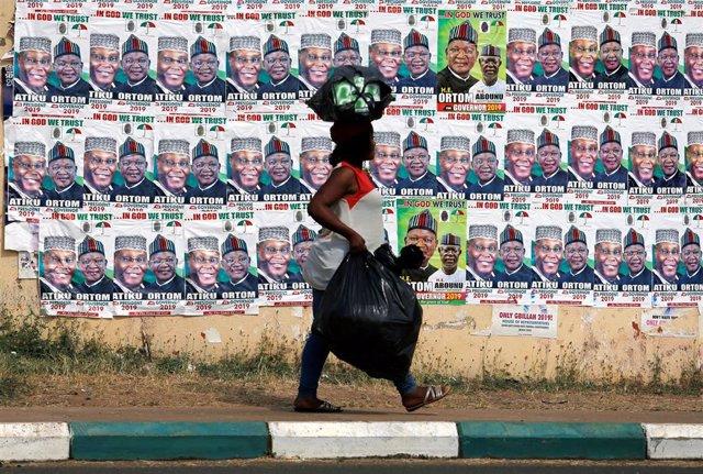 Una mujer de Nigeria camina junto a carteles electorales del opositor Atiku Abub