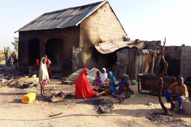 Personas junto a una casa destruida presuntamente por Boko Haram en Nigeria