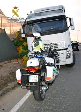 Agente de la Guardia Civil junto a la carga y el camión siniestrado