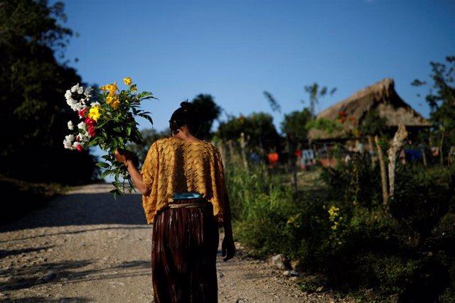 A woman walks with flowers near the home of Jakelin Caal, a 7-year-old girl who