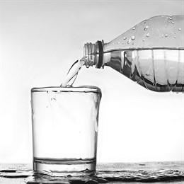 Botella de agua vertiendo a un vaso