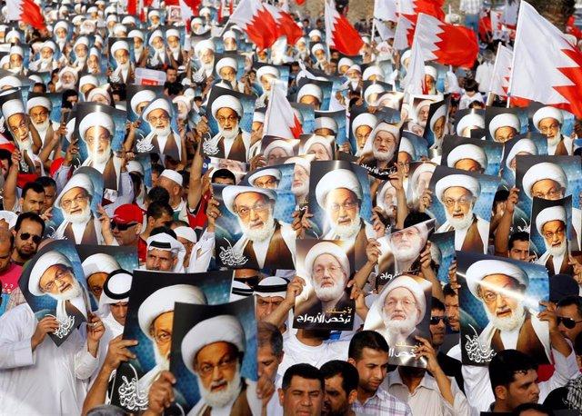 Manifestantes opositores portan la imagen de Shi'ite Ayatollah Sheikh