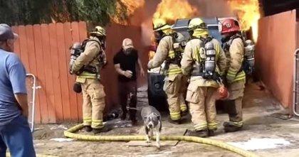 Un hombre sobrepasa la barrera de los bomberos para rescatar a su perro de su casa en llamas