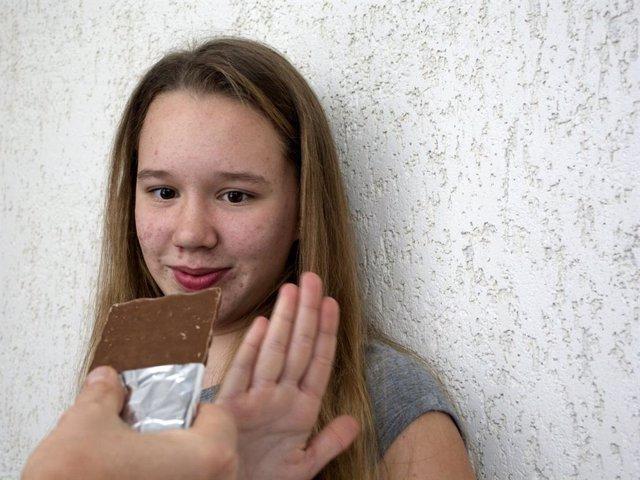 Adolescente con acné rechaza comer chocolate