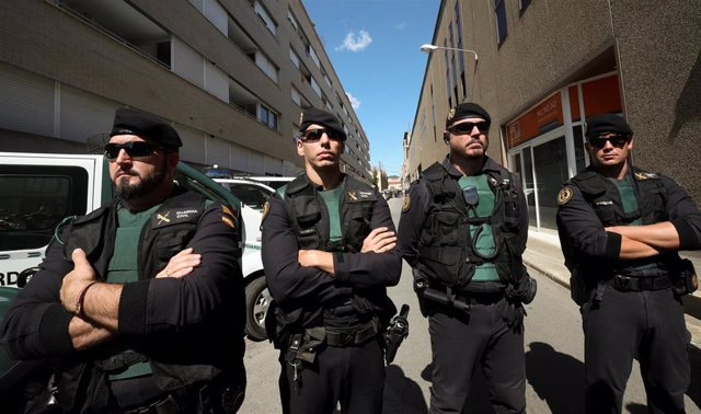 Spanish civil guards block a street next to a Unipost office which was raided in