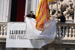 Dos treballadors de la Generalitat retiren les pancartes del Palau de la Generalitat (ACN)