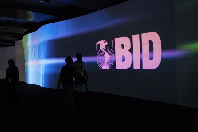 Visitors walk past a screen with the logo of Banco Interamericano de Desarrollo
