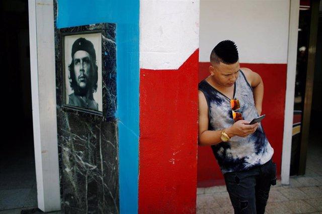 Joven cubano navegando en Internet junto a una imagen del Che