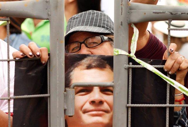 A supporter of Ecuador's former President Rafael Correa holds a photograph of Co