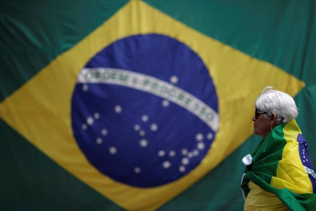 A woman is seen with a Brazilian flag in front of the National Congress during a