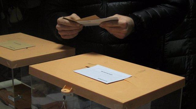 Persona con las papeletas en la mano, junto a las urnas