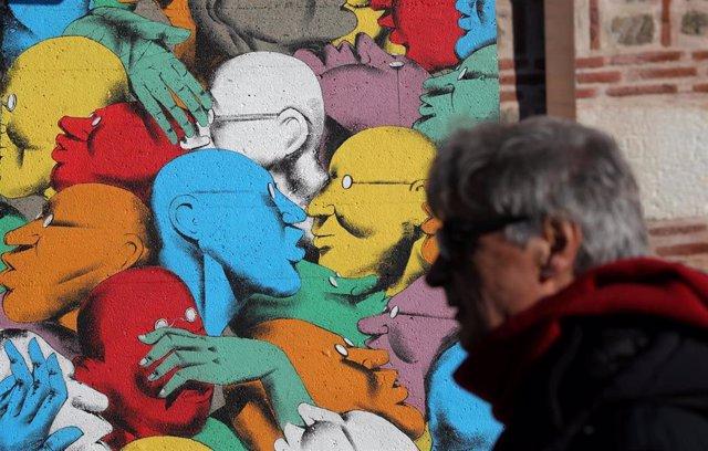 "A man walks past ""Run"" artpiece painted by Italian street artist Giacomo Bufarin"