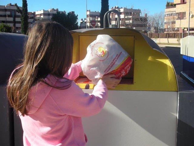 Joven deposita una bolsa de residuos de plástico en un contenedor amarillo