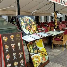Una terraza con un menú de un restaurante en la Plaza Mayor
