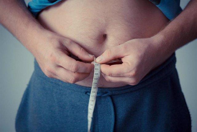 Un hombre mide su contorno abdominal