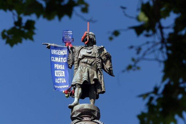 """Greenpeace despliega un cartel por la """"urgencia climática"""" en la estatua de Colón de Barcelona"""