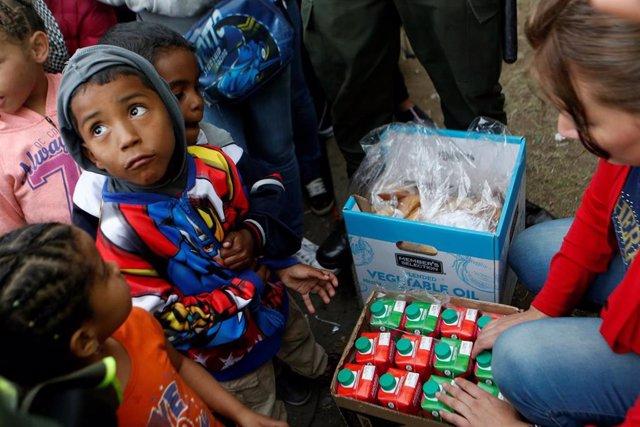 Niños migrantes venezolanos esperan a recibir comida en Bogotá