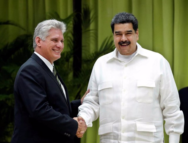Cuba's President Miguel Diaz-Canel (L) shakes hands with Venezuela's President N
