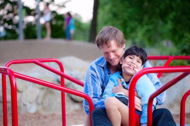 Padre en el parque con un hijo con parálisis cerebral