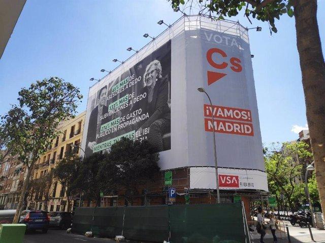 Cs coloca una lona con el cartel de campaña de Villacís en la calle Alcalá en la que arremete contra Carmena y Errejón