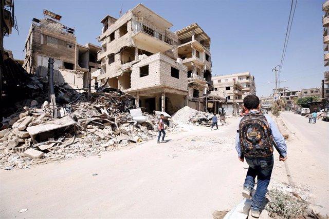 Un niño camina por Kafr Batna, en Ghuta Oriental
