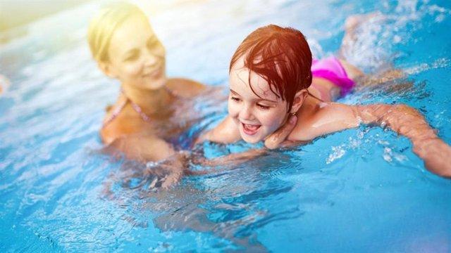 Una menor con su madre en una piscina