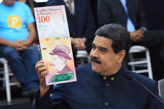 Venezuela's President Nicolas Maduro holds a sample of the new hundred bolivars