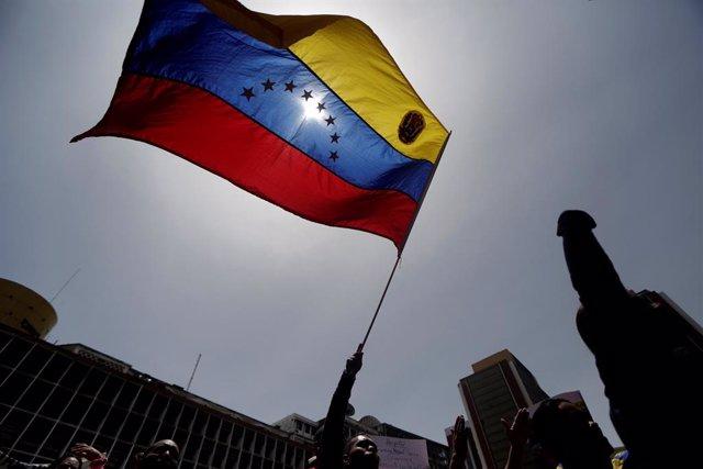 Manifestante con bandera de Venezuela en Caracas para apoyar a Maduro