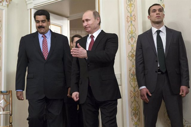 Russian President Vladimir Putin (C) shows the way to his counterpart from Venez